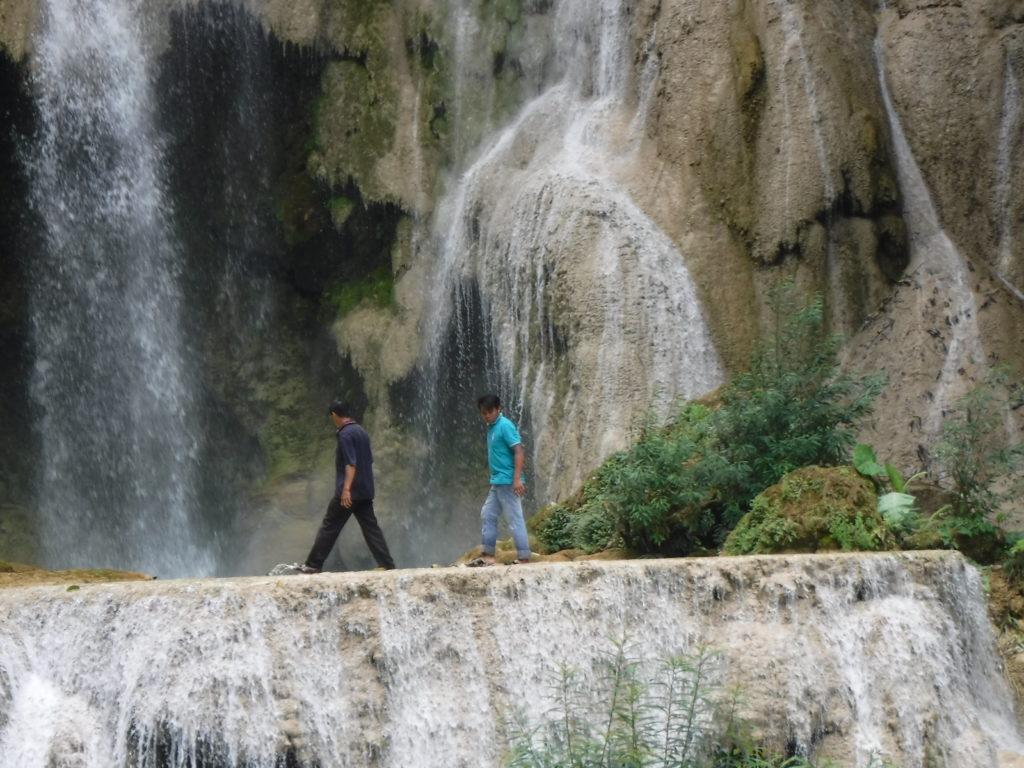 ラオス・ルアンパバーン「クアンシーの滝」の滝の中を歩く人